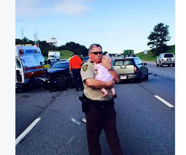 Police officer comforts baby at scene of Alabama car wreck