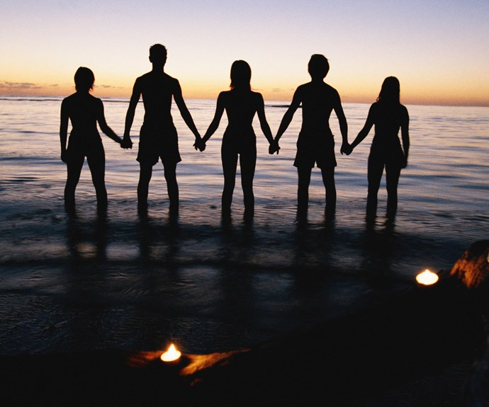 friends holding hands in the ocean