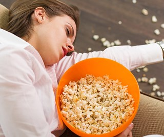 Woman in food coma with popcorn