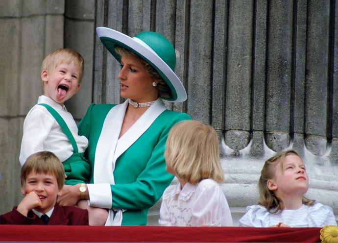 Princess Diana with her children, Prince William and [Prince Harry](http://www.nowtolove.com.au/royals/british-royal-family/prince-harry-plants-trees-with-kids-35960), watching the Trooping The Colour on the balcony of Buckingham Palace in 1988.