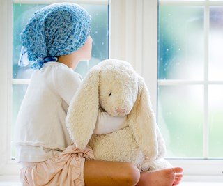 Little girl with cancer stares out window of hospital.