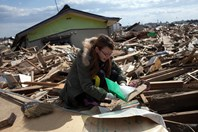 Tsunami survivor Mayu Matsukawa looks through debris at her destroyed home in Japan. (Getty)