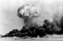 The bombing of Darwin on 19 February 1942. The HMAS <em>Deloraine</em> in the foreground wasn't damaged. (Credit: AWM)