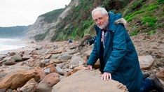 Tom Rich at Milanesia Beach with the dinosaur footprints. (Credit: Museum Victoria)