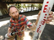 QUT researcher, Dr Richard Brown demonstrates how he was able to measure the level of water during the Qld floods. (AAP)