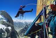 Climber swinging to his cliff camp (Credit: Bill Hatcher)