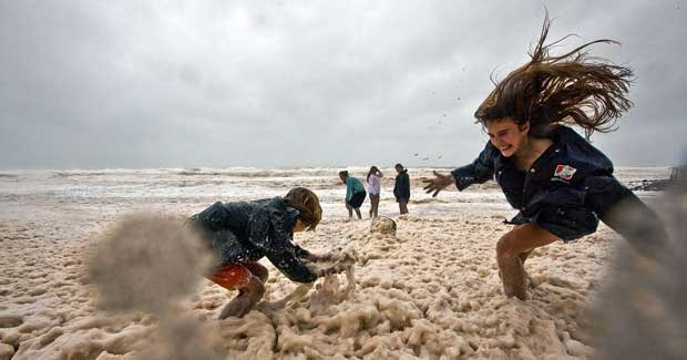 Children play in seawater frothed up by Cyclone Oswald. (Credit: Dean Saffron)