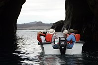 A panga (small, hard-bottomed boat) takes expeditioners through an arch near Witch Hill. (Ian Connellan)