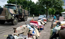 Army trucks head through the devastated streets of Chelmer in Brisbane, to transport destroyed posessions.(Photo: Carolyn Barry)