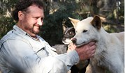 Trevor Evans shares a moment with two of the dingoes at Secret Creek