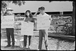 Students hold up placards with questions designed to stimulate public debate on racial discrimination outside Moree Artesian Baths and Olympic Pool, February 1965.