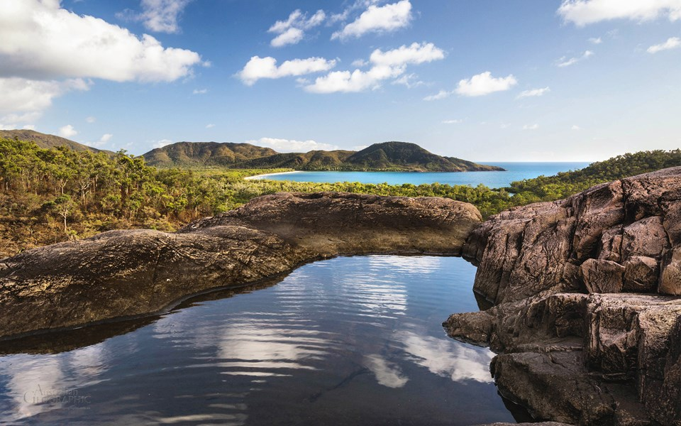 Beyond the tranquil waters atop Zoe Falls, the Coral Sea laps Hinchinbrook Island's east coast at Zoe Bay.
