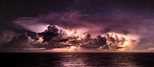A distant storm over the Pacific Ocean, complete with stars and lightning.