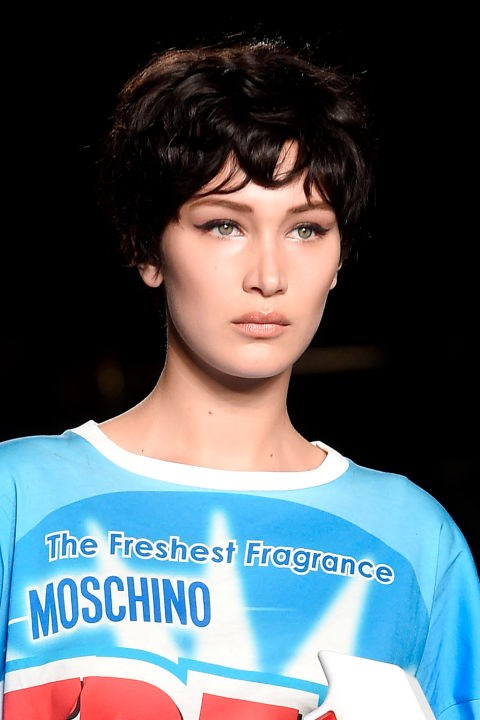 **MOSCHINO** Choppy bowl-cut wigs, in various colours, were sported at Moschino which some speculate were inspired by 90s-era supermodel Linda Evangelista. Makes sense to us. The makeup features feline flicks of liquid liner and a soft brown lip. Throwback!