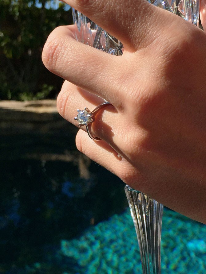 The former *The Hills* star shared up close pics of her shiny new diamond on her website. It is a classic style with a solitaire round cut diamond on a plain white gold band.