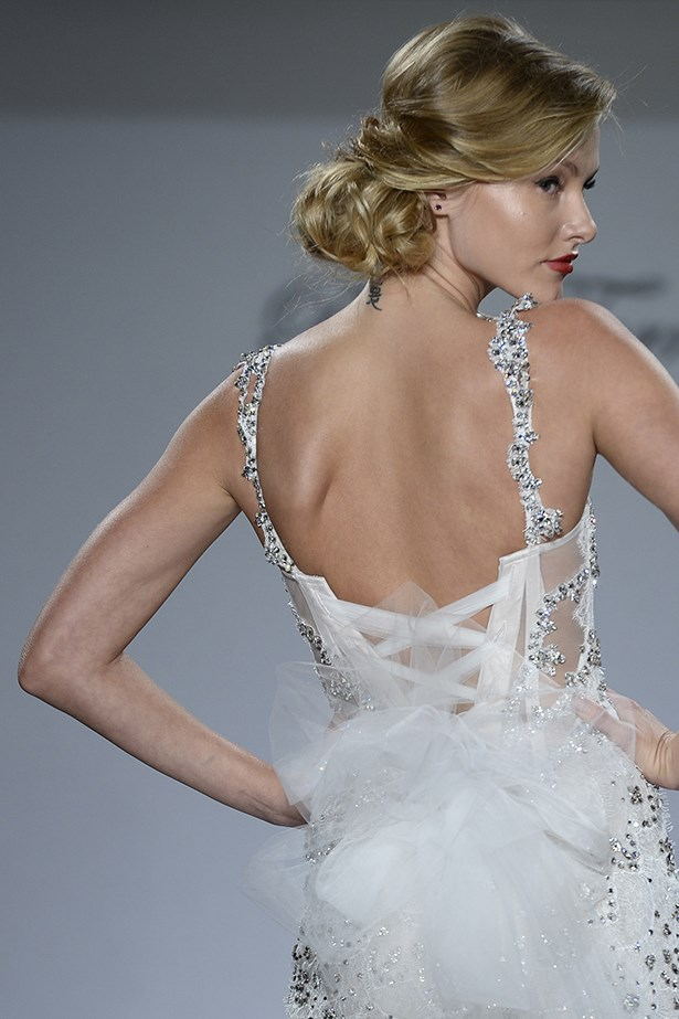 A loose, side-swept bun is both flattering and elegant for brides wanting a relaxed up-do for their big day. <br><br> Pnina Tornai for Kleinfeld bridal fashion week autumn winter 2015
