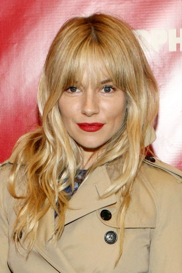 The actress pairs a classic trench with a red lip and blunt fringe in April 2013.