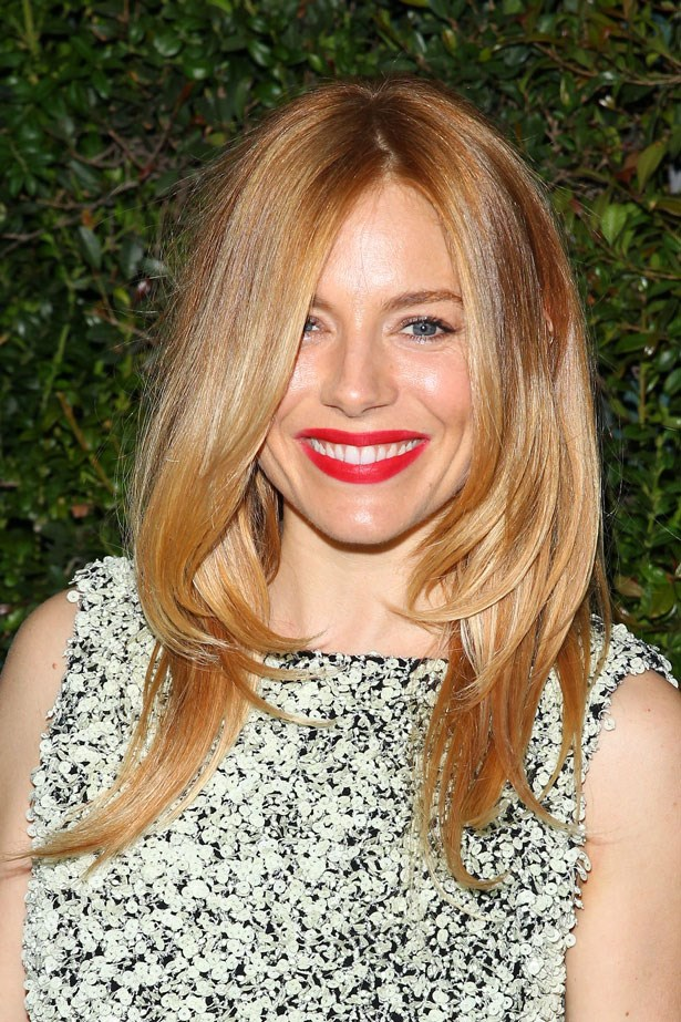 Keeping things simple with smooth, golden locks and a matte vermillion lipstick in March 2014.
