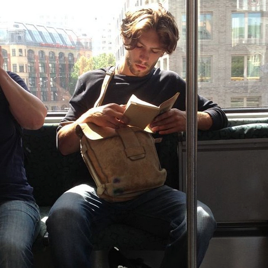 """Spotted this scruffy prince on his morning commute. Probably to sculpture class. I'm sure he's reading a collection of post-war Russian short stories, but really thinking of how he made love to his French girlfriend this morning and the gluten free toast they shared after. #marryme #hotdudesreading"" - @hotdudesreading"