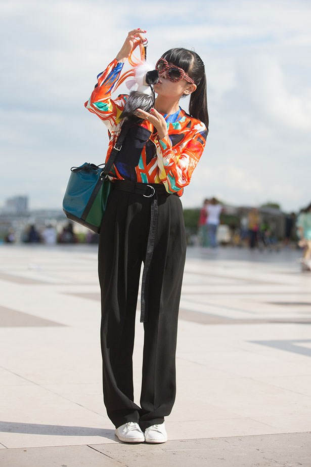 Greener kissing a Fendi Karlito acccessory, wearing a Balenciaga top, Louis Vuitton bag, Chanel sunglasses, and Adidas sneakers at Armani Prive for Paris Haute Couture Fashion Week AW 2014.