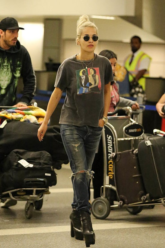 <strong>RITA ORA</strong> Ora makes a case for a casual-cool airport look with a charcoal graphic T-shirt, ripped denim, and sky-high platform boots.