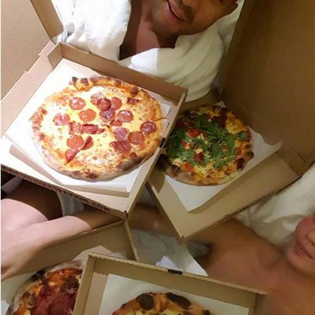 Chrissy and John eat pizza in bed, she captions it: 9.45pm update