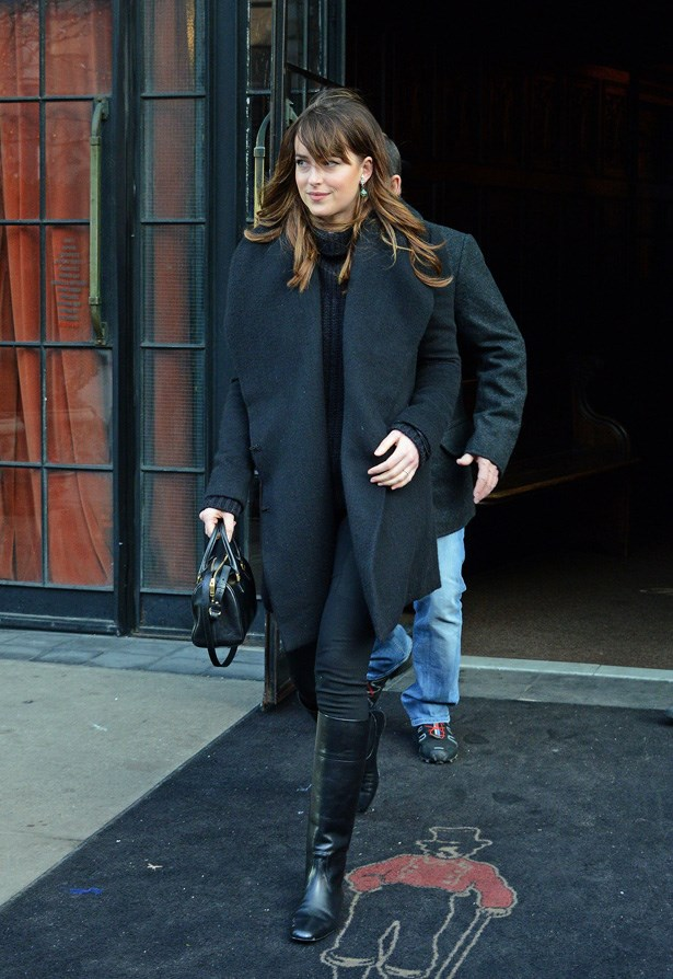 Dakota Johnson wears an over-sized boyfriend coat and knee high boots leaving her apartment in Soho.