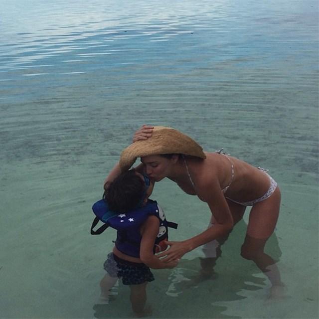 @mirandakerr plants a kiss on her son Flynn.