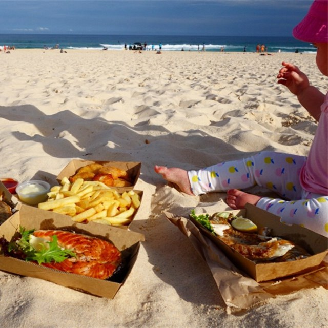 Just like any good Australian, she eats fish and chips on the beach.