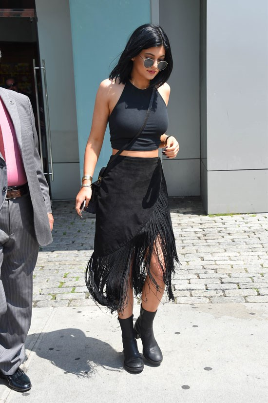 Kylie rocks a fringed suede skirt.