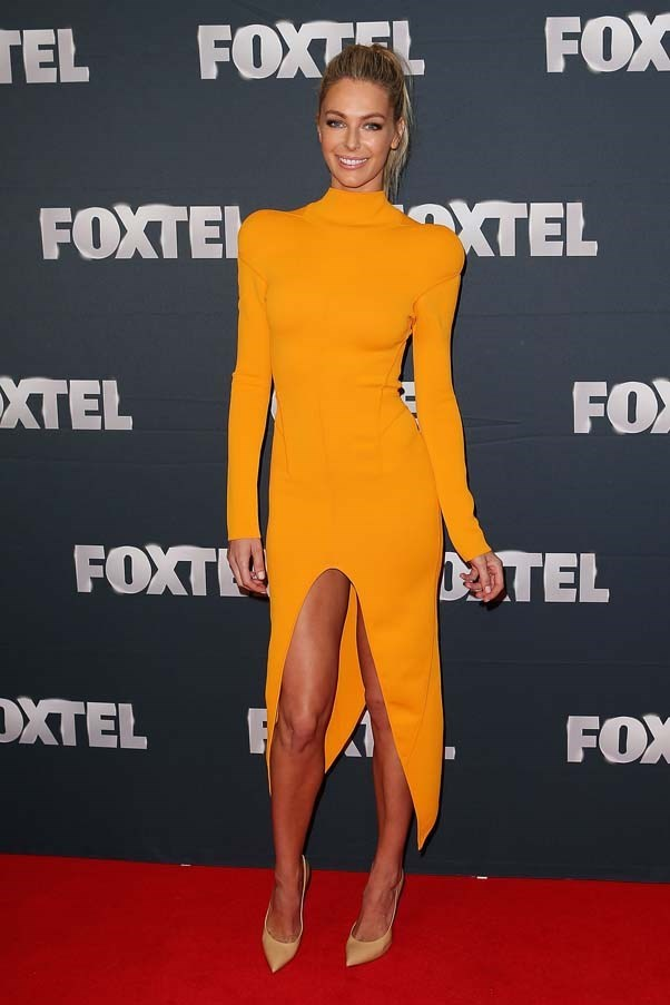 2013, February: Rocking that sun-kissed tan with a bright orange dress by Thierry Mugler at the Foxtel Launch at Fox Studios in Sydney.