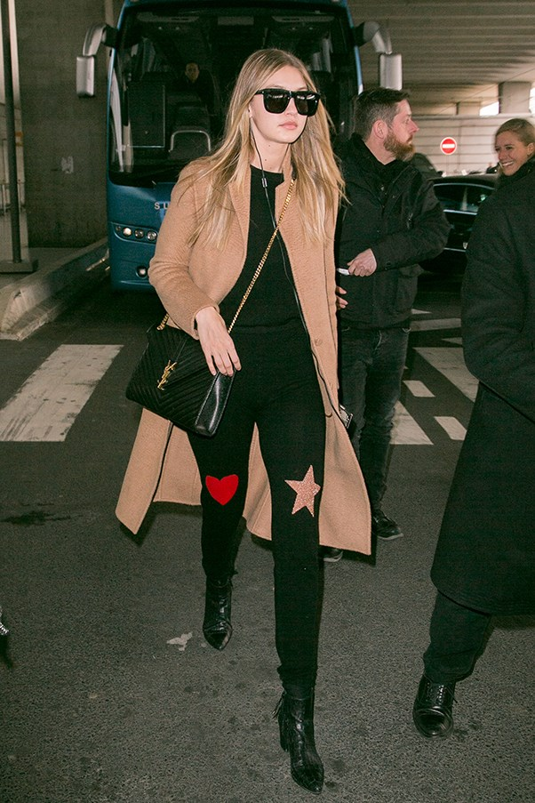 Gigi flew into Paris today wearing an adorable ensemble which consisted of star and heart patch leggings, a black sweater, her favourite Stuart Weitzman boots and a camel coat.