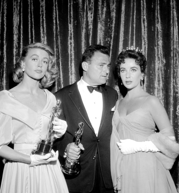 Ingrid Bergman definitely held her own next to Elizabeth Taylor in a belted and buttoned dress with short white gloves in 1956.