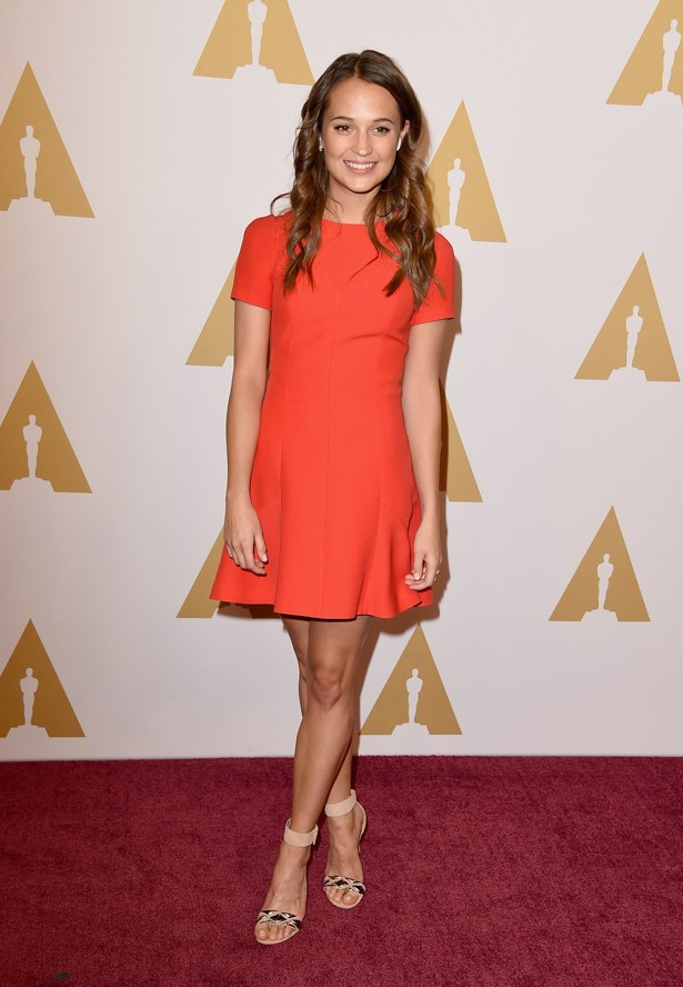 Alicia Vikander went orange in a fit and flare mini with nude strappy heels.