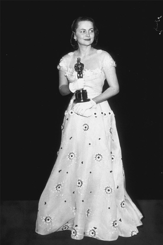 <strong>Olivia De Havilland</strong>, 1950 <br><br> <strong>Designer:</strong> Orry-Kelly <br> <strong>Why we love it:</strong> The white gloves and embellishments make for the perfect extra touches to this gown.