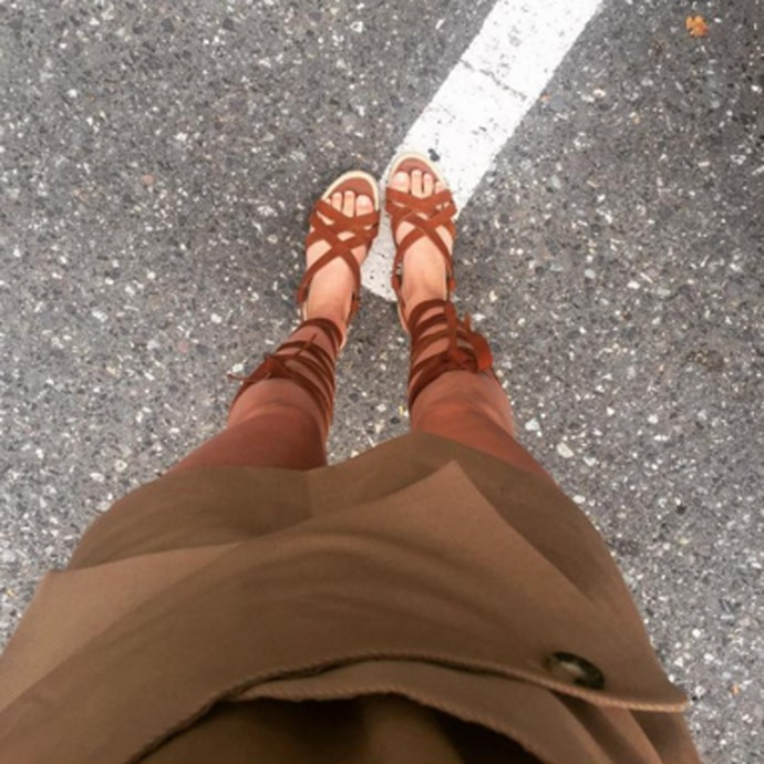 In a wrap skirt and tie-up sandals.