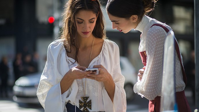 Street style women looking at iPhone.