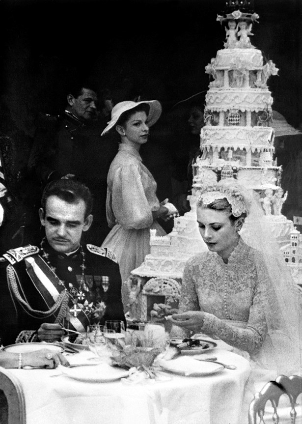 Grace and Rainier sit in front of their six-tiered cake.