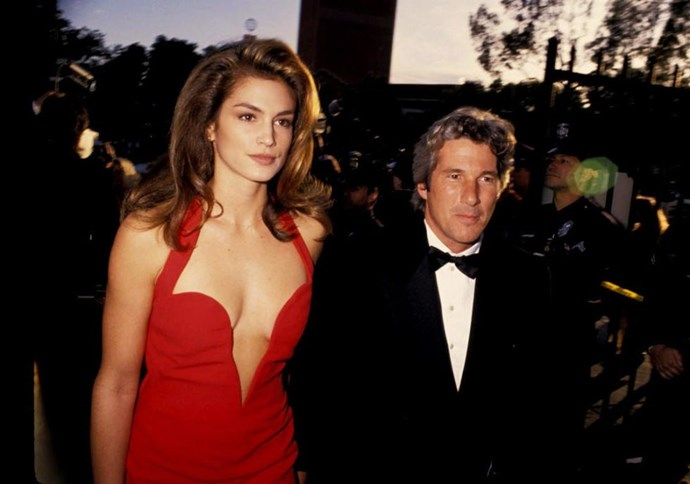 <p><strong>CINDY CRAWFORD, 1991</strong><p><p> For her first red carpet with her then-boyfriend Richard Gere, supermodel Cindy Crawford dominated the red carpet at the Academy Awards. For her all-eyes-on-me moment, she wore a scarlet Versace halter dress that featured a low cut in the front...
