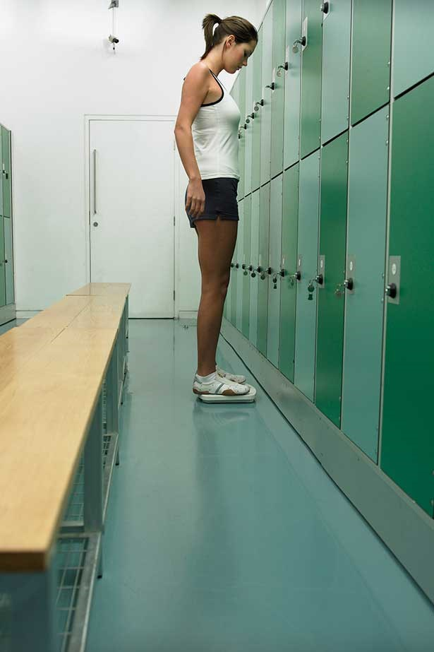 You woman on bathroom scales in gym locker room