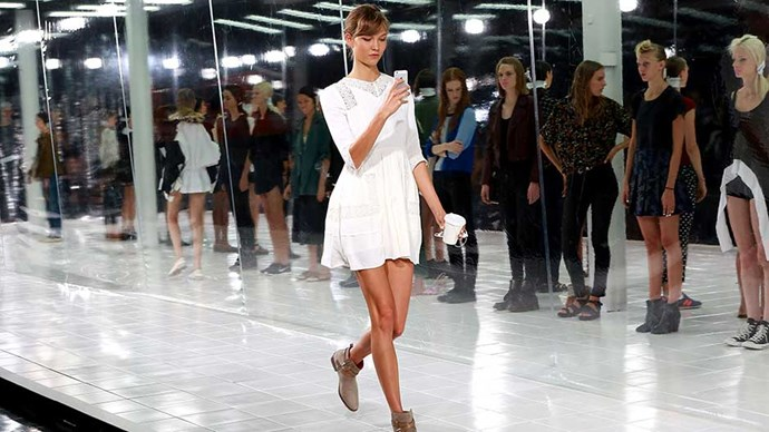 Model Karlie Kloss on her iphone during the runthrough of the Prabal Gurung show during Spring 2014 Mercedes-Benz Fashion Week