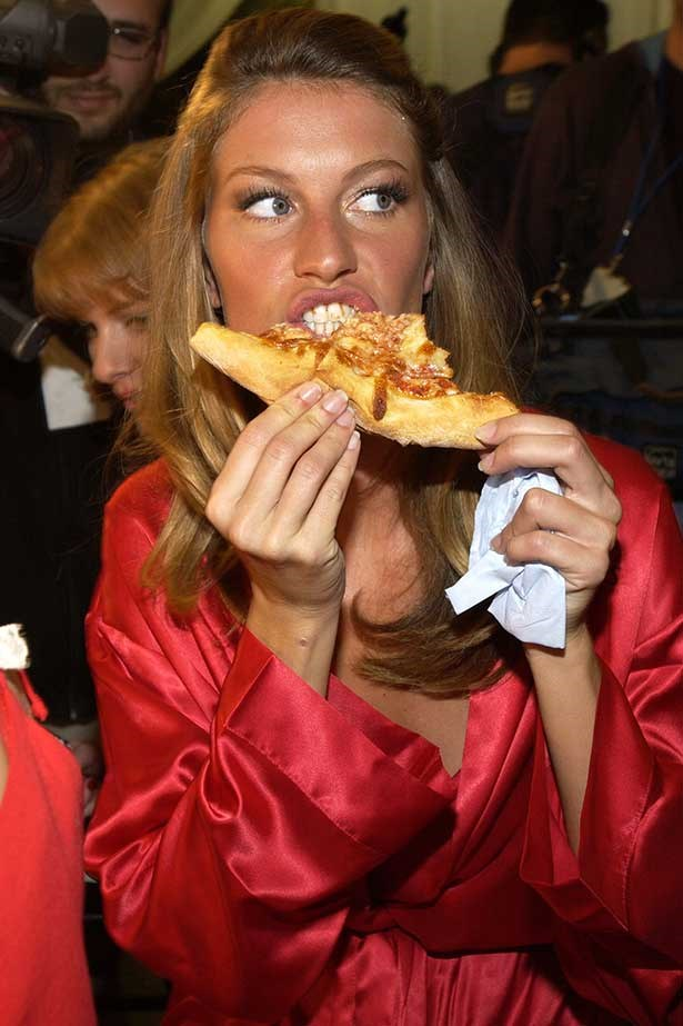 Gisele Bunchen eats pizza backstage at the Victoria's Secret Fashion Show in 2002