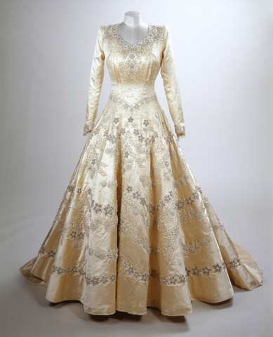 """</p><p><b>Wedding gown</b></p><p> </p><P>The queen commissioned Sir Norman Hartnell to create """"the most beautiful dress [he] had so far made"""" for her wedding to Prince Philip, the Duke of Edinburgh, in November of 1947. The ivory silk gown boasts no less than 10,000 seed pearls and a 4.6-metre train.<br><br> According to the Royal Collection Trust, British citizens were subject to rationing in 1947 following World War II, so Queen Elizabeth II collected clothing stamps to pay Hartnell for the gown."""