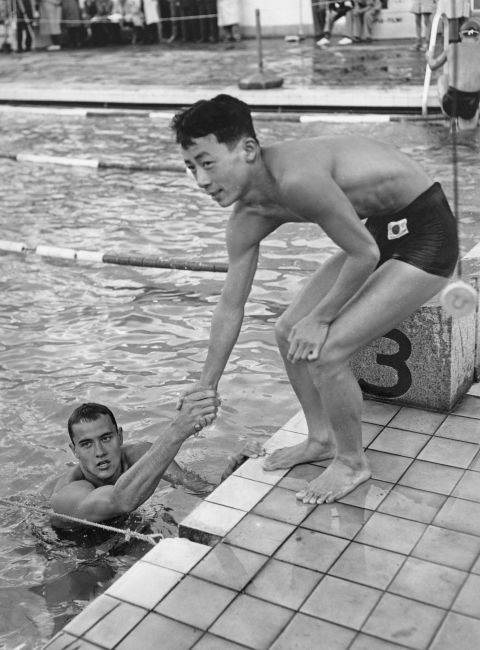 <p> <strong>1952</strong><p> <p> American swimmer Ronald Gora shaking hands with his Japanese opponent, Toru Gotu, in Helsinki following a race. In the '50s, we see the rise of functional synthetic fabrics like Spandex and Lycra that are stretchy and often used to make swimwear.