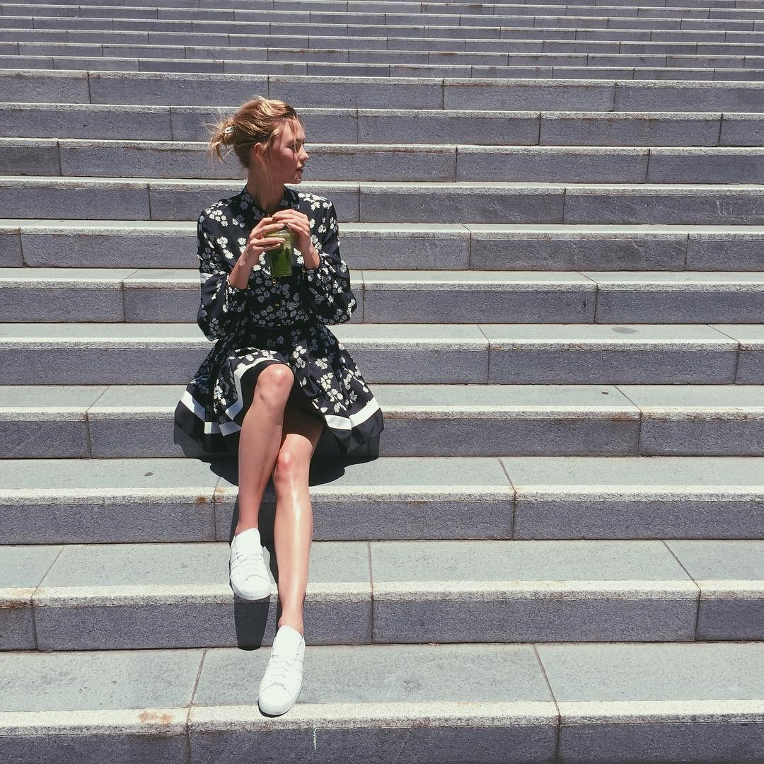 <p> Karlie balances out a printed blouse and skirt with a lived-in bun and fresh white sneakers.