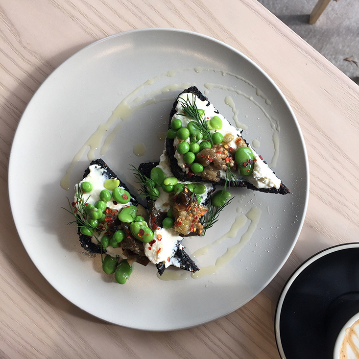 Charcoal bread with pickled eggplant, broad beans, peas and buttermilk ricotta at Cornersmith Annandale