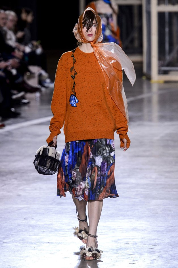 <strong>Christopher Kane</strong> <br><br> This time around, Kane's English rose has gotten stuck in the rain on her way to work, a party, a wedding—so the plastic head-wraps suggest. But these clothes and accessories can stand up to the fashion winds, he suggests. An abstracted floral came in cookie asymmetric and undone tunics and slipdresses and then in more understandable pleated skirt worn with an orange sweater with a single rose appliqué.