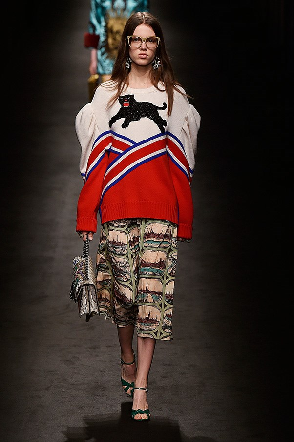 <strong>GUCCI</strong><br><br> Michele mixes and matches in a manner that feels like it could be random, though it surely is not. An intarsia sweater with a panther prancing across it is paired against a printed silk skirt, while a wallpaper floral blouse gets tucked into a black-and-white optic pleated number. Chinoiserie motifs mix with trompe l'eoil and toile.