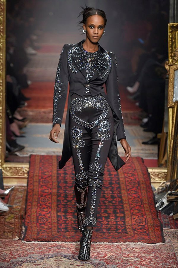<strong>MOSCHINO</strong><BR><BR> Skeleton suits were seen in the earlier '80s portion of the runway as well as in the latter fire-start segment. In the '80s, it was done via chains draped on the outside of denim and black leather to mimic ribs, hips and major bones. On a peak-shouldered black satin tuxedo, crystals replaced bone. Weird? Yes. But also kind of cool. And it wouldn't be the worst thing to see Lady Gaga rock this at the Oscars when everyone else will be doing the expected... Just saying.