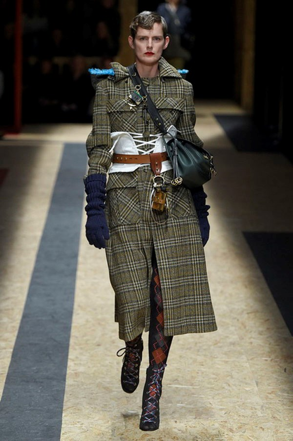 <strong>PRADA</strong><BR><BR> Stella Tennant looked majestic—by the tilt of that chin, proud—in a moss Scottish plaid field coat and red plaid tights. The relatively pared down look brought into view the accessories, which deserve a review of their own. Keys and leather-bound books dangled from thick chain necklaces, belts and from straps of cross-body bags. Nearly every bag was intricately detailed with layers of leather flowers. Shoes were high and either hiking boots—because obviously this lady has conquered Himalaya, patent buckled booties, and tons of ankle-strap wedges, all worn with patterned tights.